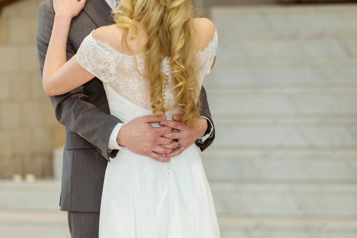 grooms hands clasped around bride's waist
