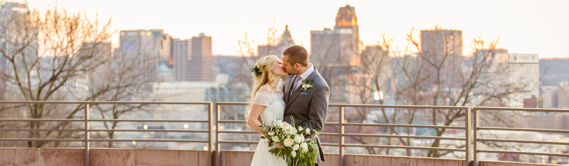Bride and groom kissing at sunset with the Cincinnati skyline in the background
