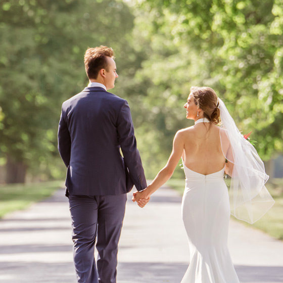 Couple walking hand in hand down tree lined drive