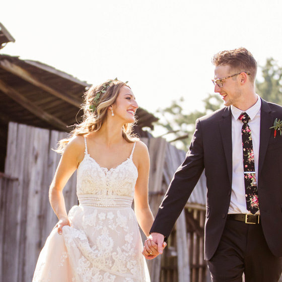 Bride and groom walking in front of an old log barn