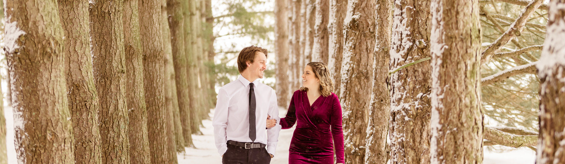 Engaged couple walking through a pine forest